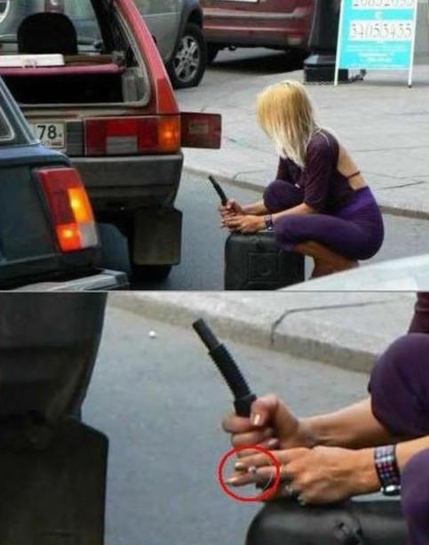 Eine junge Frau will Benzin mit einem Reservekanister in ihr Auto füllen. Sie hat den Kanister geöffnet und hält eine dabei eine brennende Zigarette in der Hand.
