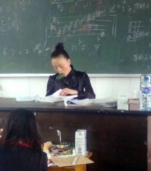 Eine Asiatian, offensichtlich eine Musiklehrerin, hat eine Gurke im Mund.