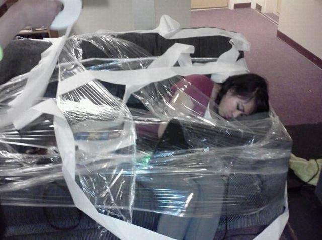 Eine Frau wurde auf einem Sofa sitzend und schlafend mit Frischhaltefolie eingepackt.