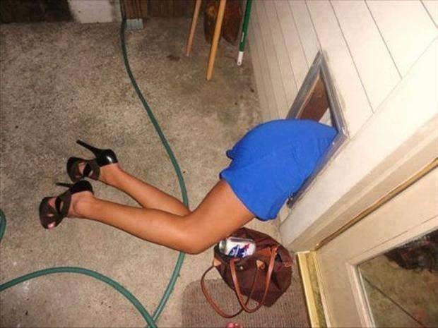 Von einer Frau sind nur noch die Beine und die High Heels zu sehen. Der Oberkörper steckt in einer Katzenklappe.
