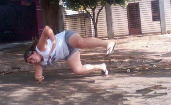 Eine etwas füllige Frau versucht in Sandalen Skateboard zu fahren. Das geht natürlich schief und sie stürzt zu Boden.