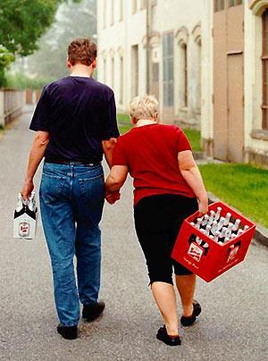 Ein Mann trägt ein Sixpack, seine Frau eine Kiste Bier.