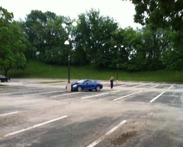 Eine junge Frau hat mit ihrem Sportwagen auf einem großen leeren Parkplatz die einzige Laterne gerammt.