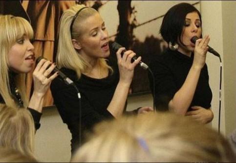 Drei Frauen singen in Mikrofone. Eine schwarzhaarige Frau scheint das Mikro zu verschlucken, sie hat es weit in ihren Mund gesteckt.