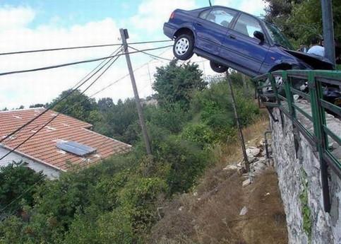 Ein Auto hängt schief über einem Geländer und einem Abhang.