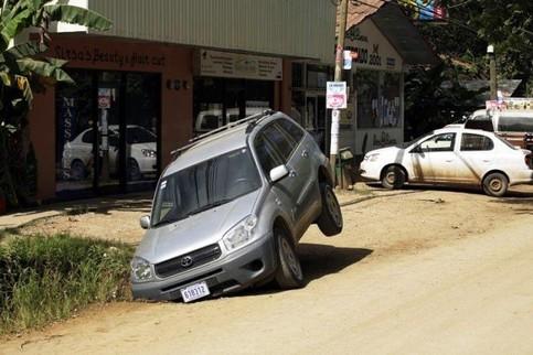Ein Auto ist mit dem rechten vorderen Rad in ein Loch gefahren und hängt fest.