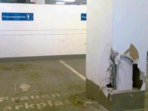 In einem Parkhaus ist ein Frauenparkplatz. Die Säule neben dem Parkplatz ist beschädigt und wurde scheinbar von einer Frau beim Einparken angefahren.