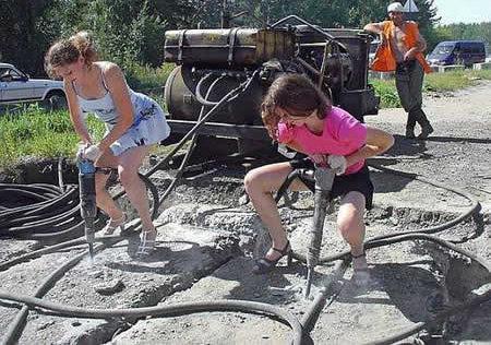 Zwei Frauen in sommerlicher Kleidung haben sich auf einer Baustelle zwei große Bohrer geschnappt und demonstrieren dem Bauarbeiter, wie gut sie mit diesem Werkzeug umgehen können.