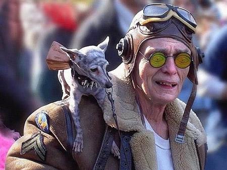 Ein merkwürdig gekleideter Opa mit einem merwürdigen Hund.