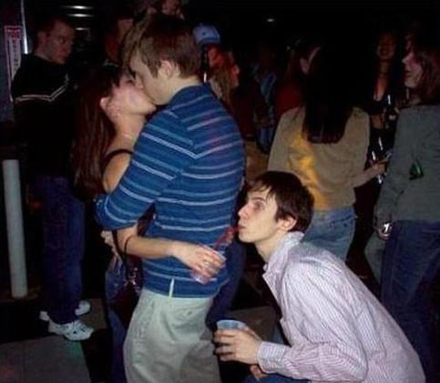 Ein Pärchen küsst sich. Während sie ihre Hand mit einem Getränk hinter dem Rücken ihres Partners hält, kniet dort ein anderer Mann und trinkt heimlich mit einem Strohhalm ihr Getränk.