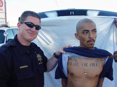 """Ein Polizist zeigt stolz einen Gefangenen, auf dessen Brust """"Fuck the Police"""" tätowiert ist."""