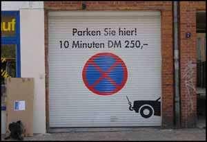 """Ein Garagentor mit der Aufschrift """"Parken Sie hier! 10 Minuten DM 250,-"""""""