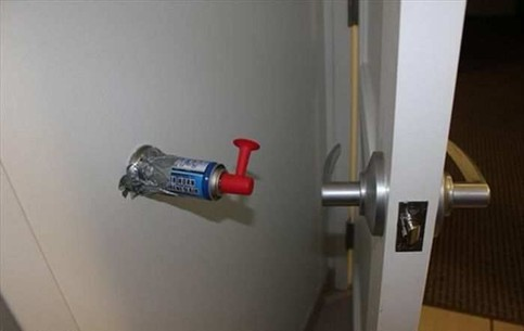 An einer Wand ist auf Höhe der Türklinke einer Tür eine Gashupe befestigt. Wenn nun jemand die Tür weit öffnet, wird ein ohrenbetäubender Lärm ertönen.