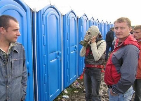 Eine Frau geht mit einer Gasmaske auf eine Dixie-Toilette.