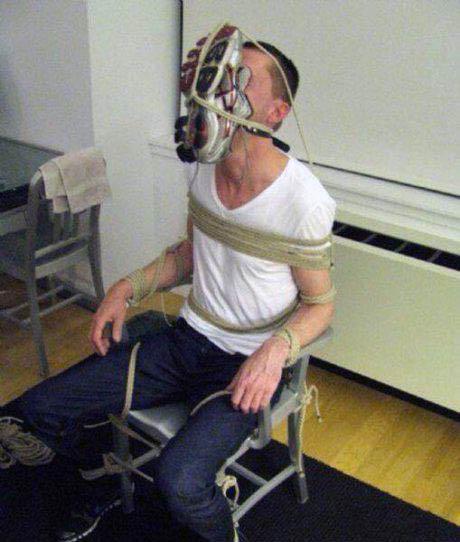 Ein Mann wurde an einen Stuhl gefesselt. Zusätzlich wurde ihm ein Turnschuh vor das Gesicht gebunden.