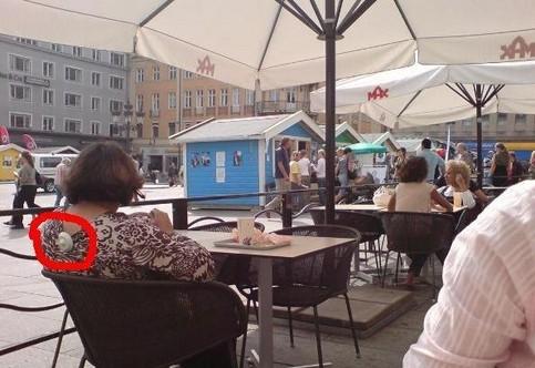 Eine Frau in einem Café, an ihrem Hemd hängt noch der Sicherungsmechanismus aus dem Kaufhaus.