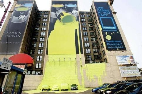 Eine Werbung, die aussieht, als sei ein Eimer gelber Farbe von einem Haus auf Autos gekippt.