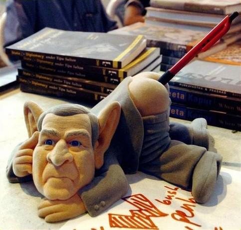 Ein Bleistiftspitzer in Form von George W. Bush, den man den Bleistift in den Popo schieben kann.