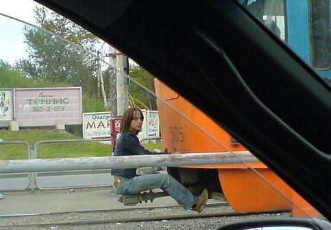 Eine Frau sitzt hinten auf einer Strassenbahn und fährt schwarz.