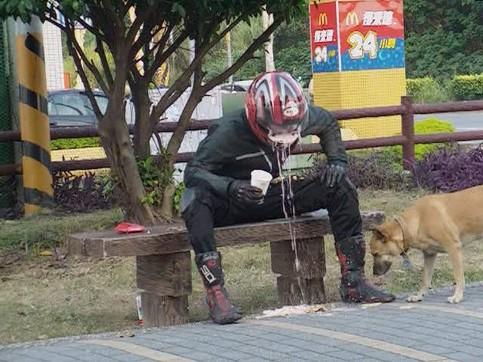 Ein Motorradfahrer mit Helm hat einen Schluck aus einem Getränkebecher genommen, nun sprudelt das Getränk aus seinem Helm heraus.