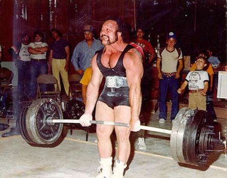 Ein Gewichtheber stemmt ein Gewicht. Dabei verzieht er sein Gesicht.