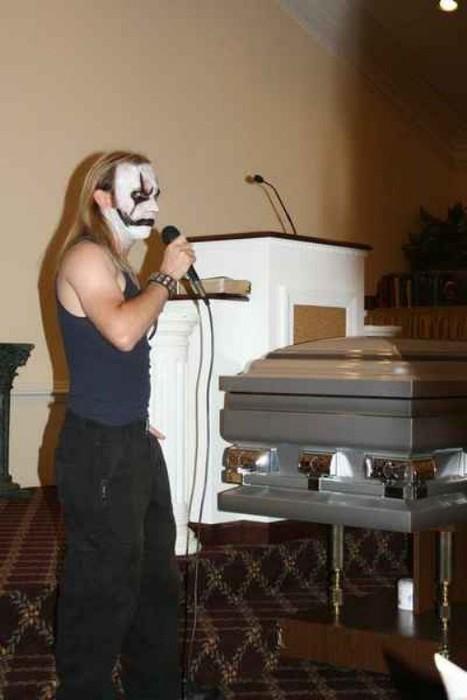 Ein düster geschminkter Mann hält eine Rede auf einer Beerdigung.