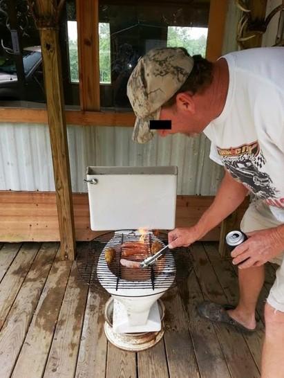 Ein Mann grillt Würstchen auf einem Rost, der auf einer Klobrille liegt.