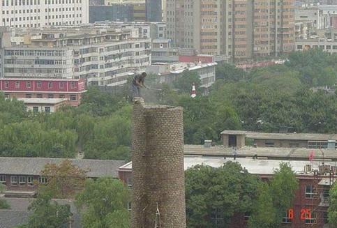 Ein Mann steht auf dem Rand eines extrem hohen Schornsteins und scheint etwas über dem Schlot zu grillen.
