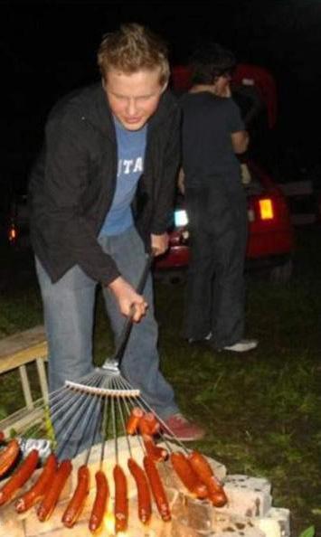 Ein Mann grillt Würstchen, die auf einem Rechen aufgespiesst sind.