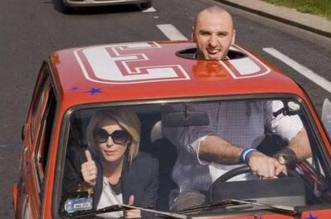 Ein großer Mann sitzt am Steuer eines kleinen Autos. Das Auto hat ein Loch über dem Fahrersitz, so dass der Mann aus diesem Loch herausschauen kann.