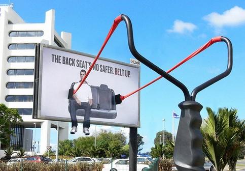 Ein Werbeplakat, auf dem ein Mann an einem Katapult befestigt ist, und das für das Anschnallen im Auto wirbt.
