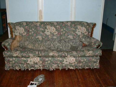 Ein Soldat liegt in Tarnkleidung auf einem Sofa und ist so kaum sichtbar.