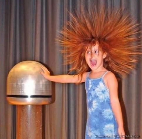 Einem Kind stehen die Haare zu berge, als es einen elektrostisch geladenen Metallpilz berührt.