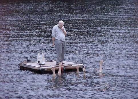 Ein Mann auf einem Floß, vor ihm recken Leute Hände aus dem Wasser.
