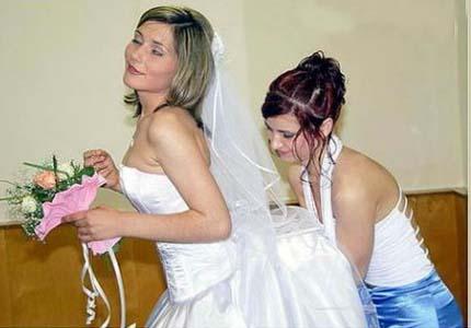 Eine Frau greift einer Braut unter das Brautkleid.