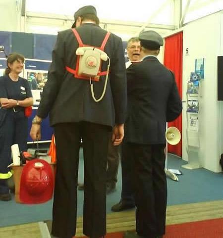 Ein Mann trägt ein altmodisches Telefon mit Wählscheibe auf seinem Rücken geschnallt.