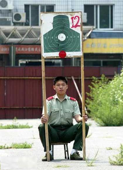 Ein Chinese hält eine Zielscheibe zum Schiessen hoch.