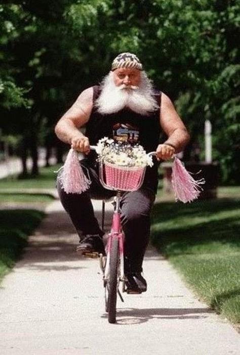 Ein bärtiger Rocker fährt auf einem rosa Fahrrad.