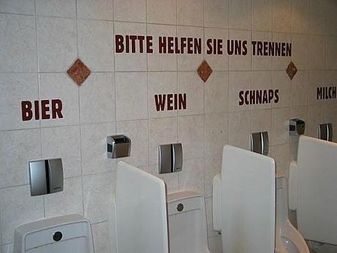 """Auf einer Herrentoilette sind die verschiedenen Pissoirs beschriftet mit """"Bier, Wein, Schnaps, Milch"""". Darüber steht """"Bitte helfen sie uns trennen""""."""