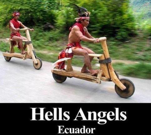 Zwei Indios fahren mit Rollern aus Holz einen Berg hinab.