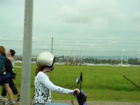 Eine Frau hat einen Motorradhelm falsch rum auf.