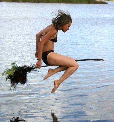 Eine junge Frau springt mit einem Stock zwischen den Beinen, so dass es aussieht, als würde sie auf einem Besen fliegen