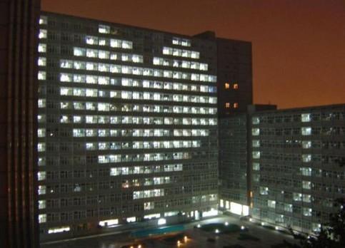 In einem Hochhaus sind nachts die Fenster in Herzform erleuchtet.