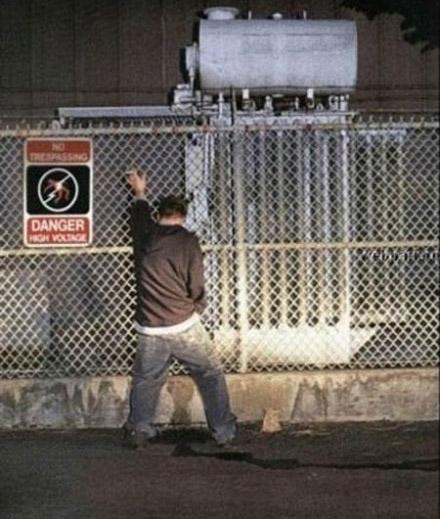 Ein Mann pinkelt an einen Zaun, an dem ein Schild hängt, dass vor Hochspannung warnt.