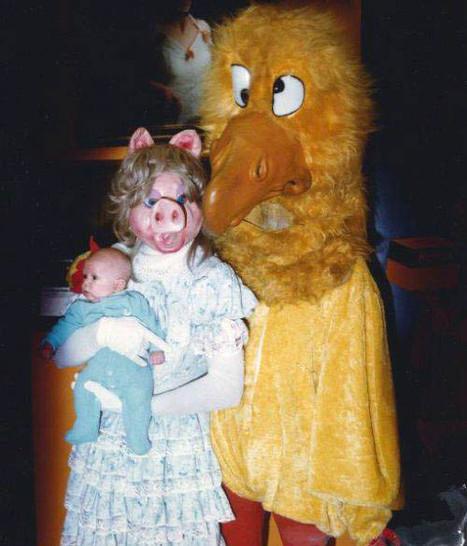 Ein Mann und eine Frau sind sehr gruselig verkleidet. Sie ist ein Schwein, er ein Vogel. Die Frau hält ein Baby in ihren Armen.
