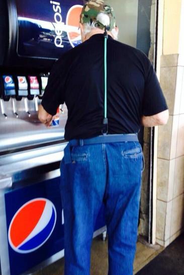 Ein Mann hält seine Hose vom Runterrutschen ab, indem er einen Spanngurt zwischen seiner Mütze und seiner Hose gespannt hat.