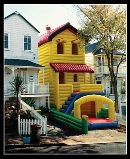 Eine Hüpfburg steht zwischen zwei Häusern. Sie sieht aus wie ein Haus.