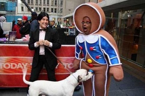 Ein Hund beißt einen Mann, der in einem Kostüm steckt, zwischen den Beinen. Der Mann macht einen erstaunten Gesichtsausdruck.