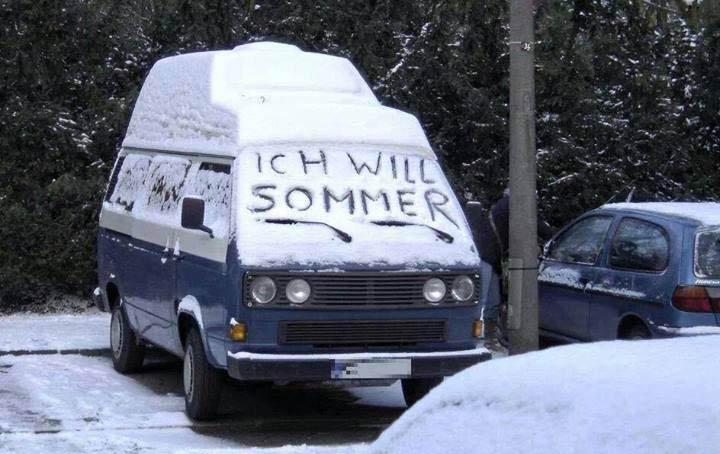"""Ein Campingbus ist mit Schnee bedeckt. Jemand hat in den Schnee auf der Frontscheibe """"Ich will Sommer"""" geschrieben."""
