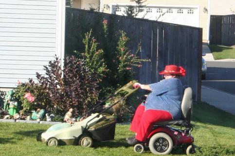 Eine dicke Frau fährt in einem elektrischen Rohlstull und mäht dabei den Rasen.
